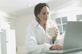 Woman in a bathrobe types at a laptop.
